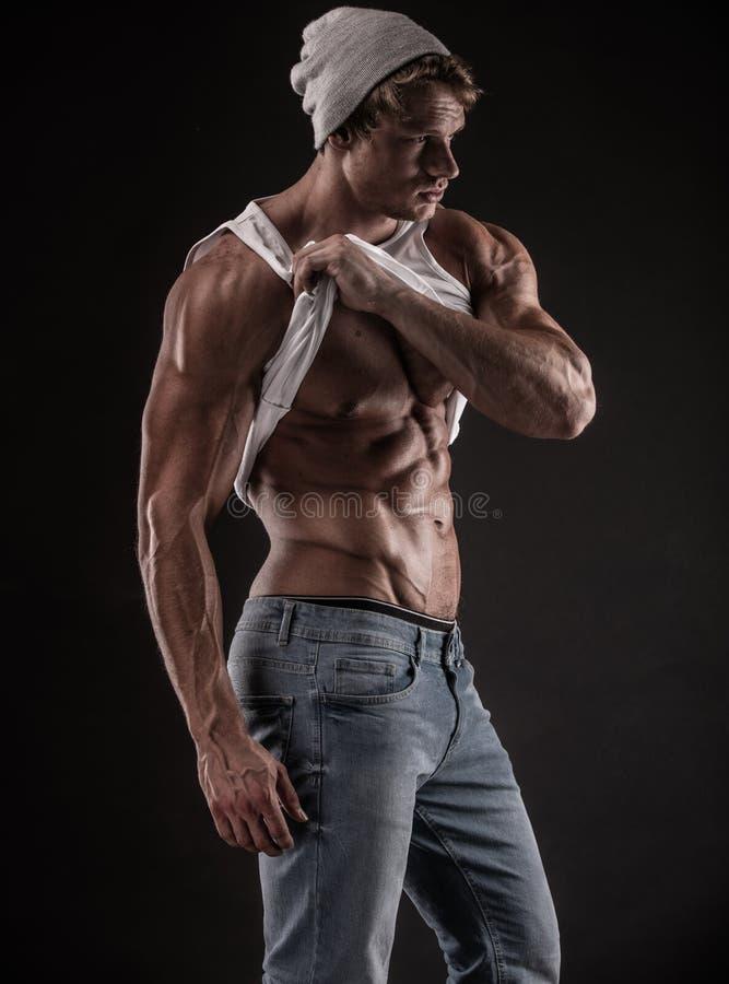 Retrato do homem atlético forte da aptidão sobre o fundo preto fotos de stock royalty free