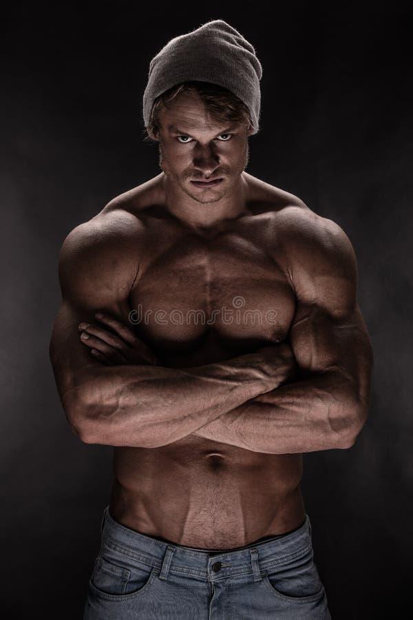 Retrato do homem atlético forte da aptidão sobre o fundo preto imagens de stock