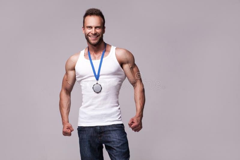 Retrato do homem atlético na camiseta branca com medalha dos campeões foto de stock royalty free