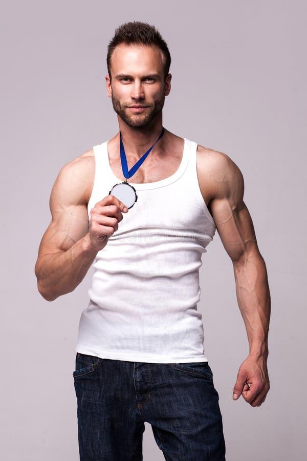 Retrato do homem atlético na camiseta branca com medalha dos campeões imagem de stock royalty free