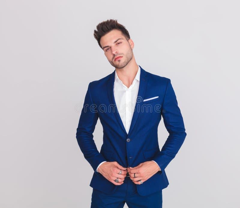 Retrato do homem atrativo orgulhoso que abotoa seu terno azul fotos de stock