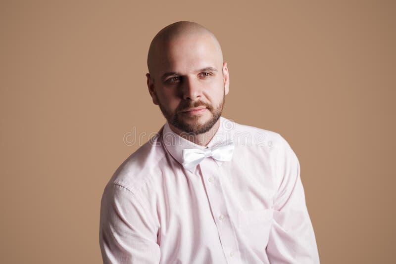 Retrato do homem calvo farpado considerável na luz - camisa e wh cor-de-rosa fotografia de stock