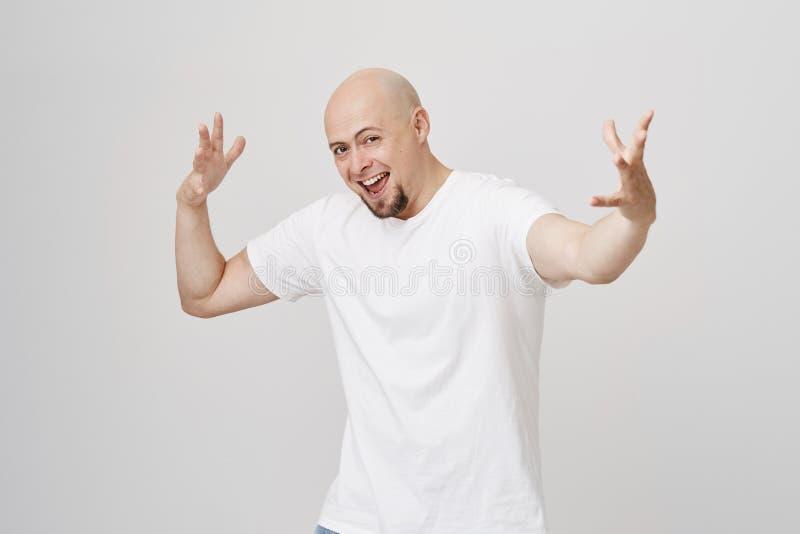 Retrato do homem caucasiano calvo entusiasmado brincalhão com a barba que faz gestos estranhos como se dançando ou moldando o per foto de stock