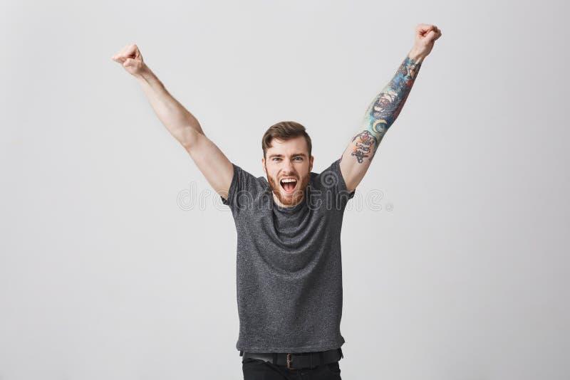 Retrato do homem caucasiano encorajador feliz bonito com barba e mãos de aumentação tattooed do braço, gritando no volume complet imagens de stock