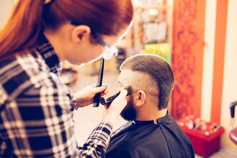 Retrato do homem caucasiano farpado novo considerável que obtém o corte de cabelo na moda na barbearia moderna foto de stock royalty free