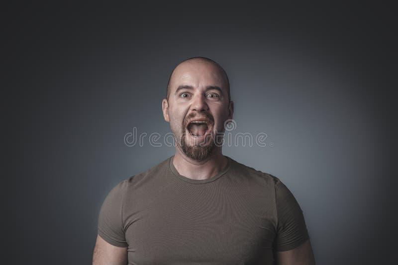 Retrato do homem caucasiano que grita e que olha em linha reta na frente da câmera imagem de stock royalty free