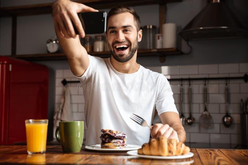 Retrato do homem caucasiano 30s que toma a foto do selfie no telefone celular ao comer o café da manhã em casa fotos de stock royalty free