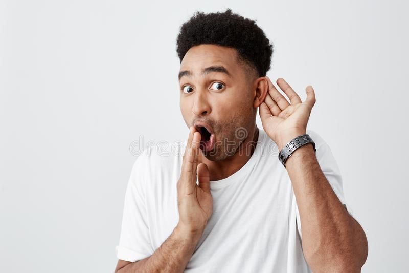 Retrato do homem chocado preto-descascado bonito maduro com penteado afro no t-shirt branco ocasional que guarda a mão próximo foto de stock