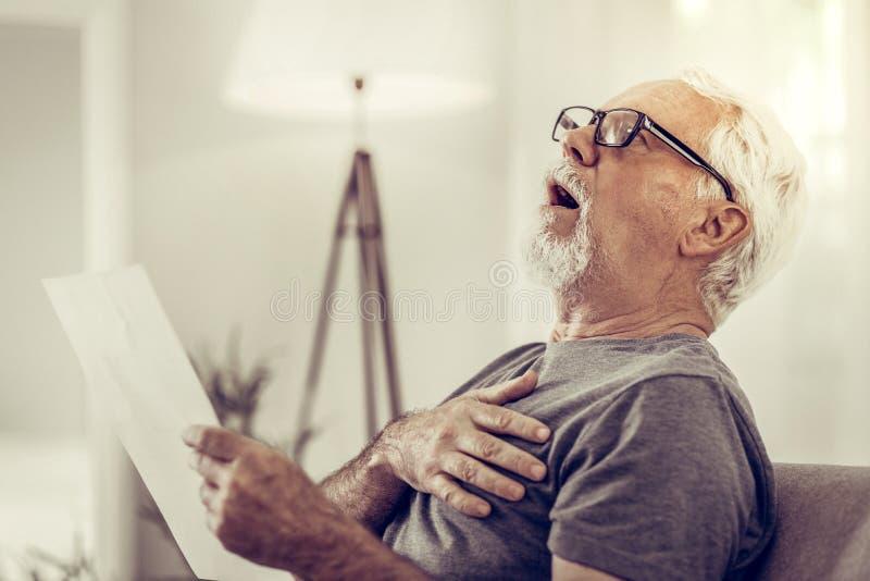 Retrato do homem chocado que está sendo surpreendido em papéis nas mãos imagens de stock royalty free