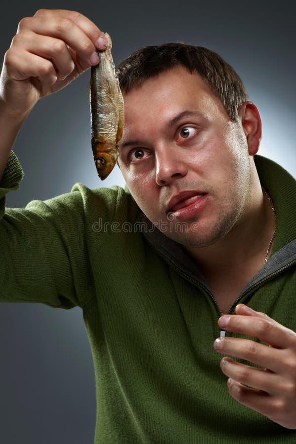 Retrato do homem com fome que olha fixamente em peixes imagens de stock royalty free