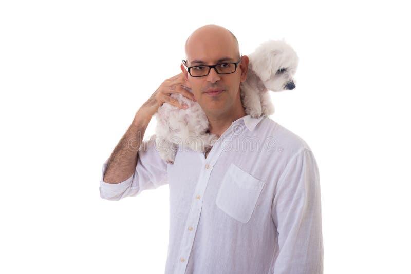 Retrato do homem com os vidros que guardam o cão maltês em seu pescoço imagem de stock royalty free