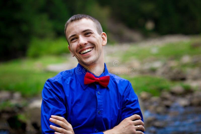 Retrato do homem considerável de sorriso dos jovens na camisa azul perto do rio da floresta fotografia de stock royalty free