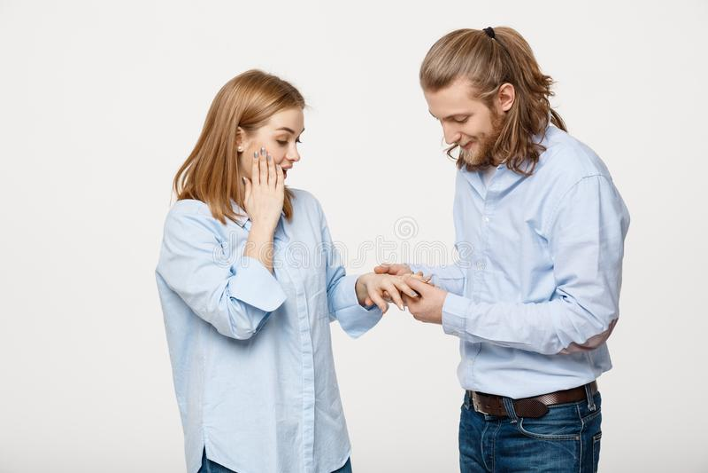Retrato do homem considerável deleitado alegre que veste um anel de noivado para sua amiga sobre o fundo branco isolado fotos de stock royalty free