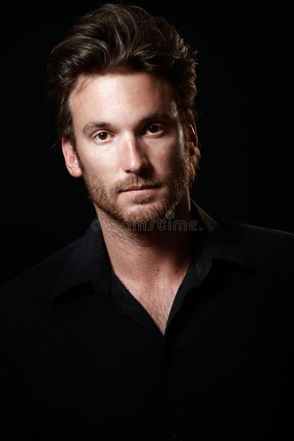 Retrato do homem considerável no preto fotografia de stock royalty free