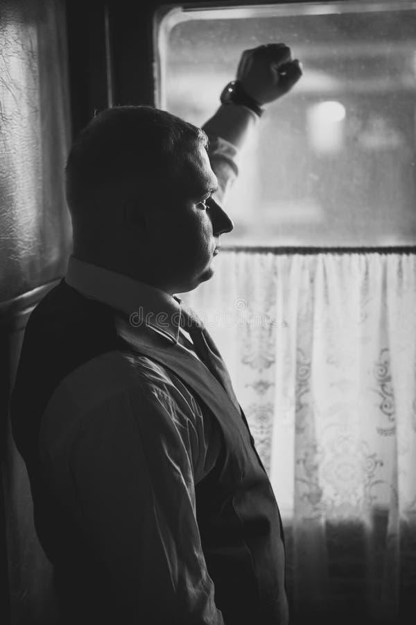 Retrato do homem considerável no terno que olha fora da janela em retro fotos de stock