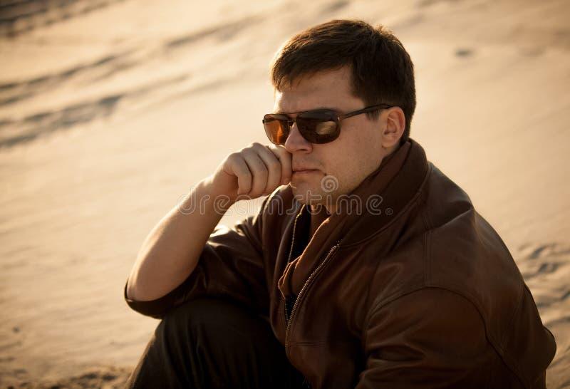 Retrato do homem considerável nos óculos de sol que sentam-se na duna de areia fotografia de stock