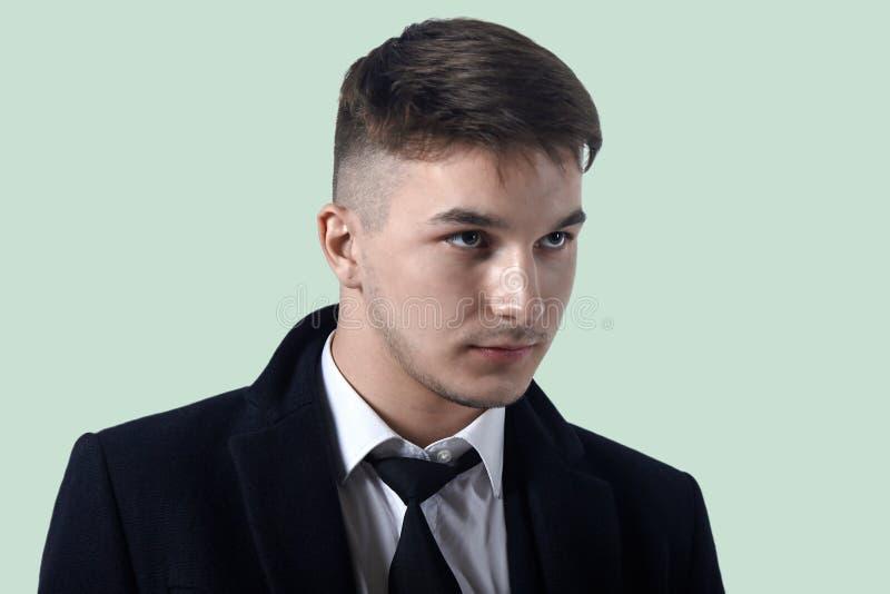 Retrato do homem considerável novo com olhar atento no fundo claro Penteado na moda, emoções fortes, barba pequena, o clássico imagem de stock