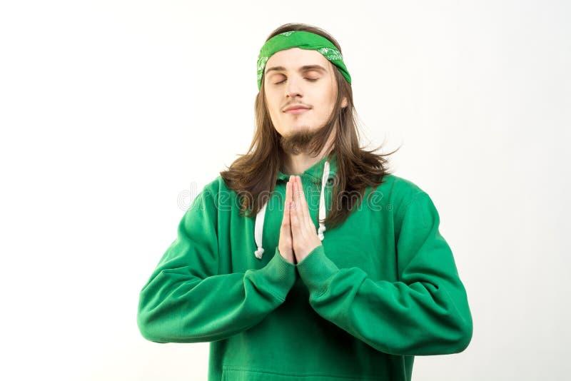 Retrato do homem considerável novo no hoodie verde com um sorriso calmo, uns olhos fechados e mostrar o fundo do branco dos again imagens de stock