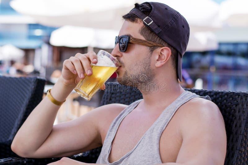 Retrato do homem considerável novo que bebe a cerveja de refrescamento fria imagem de stock royalty free
