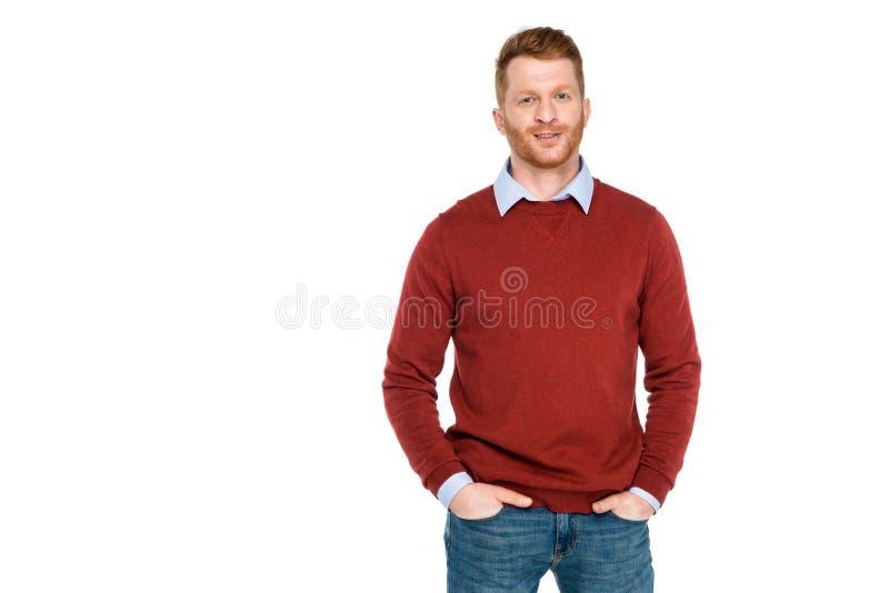 retrato do homem considerável do ruivo que está com mãos em bolsos e que sorri na câmera foto de stock