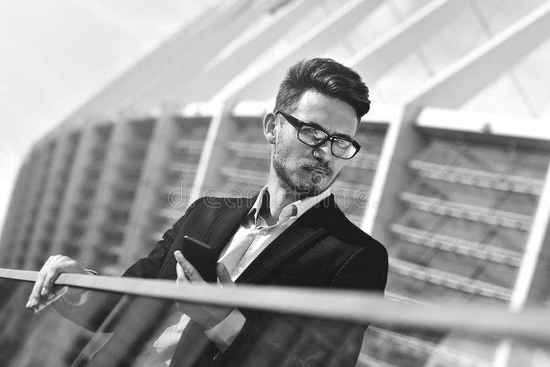 Retrato do homem considerável seguro com telefone, no terno elegante, homem de negócios bem sucedido imagens de stock