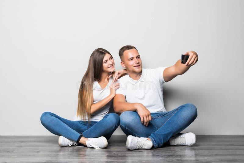 Retrato do homem consider?vel e da mulher dos pares alegres que sentam-se no assoalho junto e que tomam o selfie no smartphone is imagens de stock royalty free