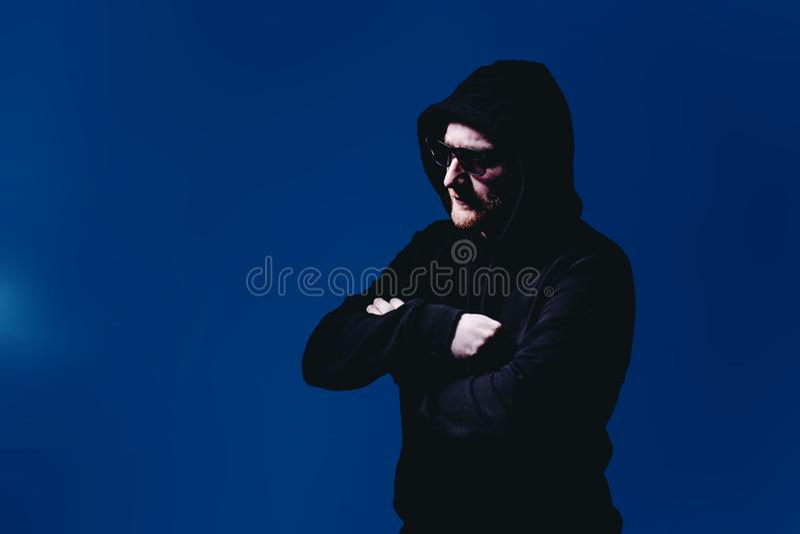 Retrato do homem da forma em uma camiseta preta com uma capa e os óculos de sol na luz de néon no estúdio imagem de stock royalty free