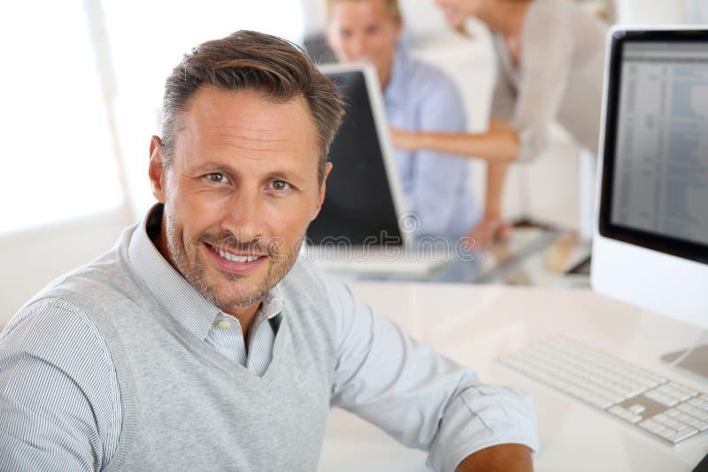Retrato do homem de meia idade que trabalha com computador fotografia de stock