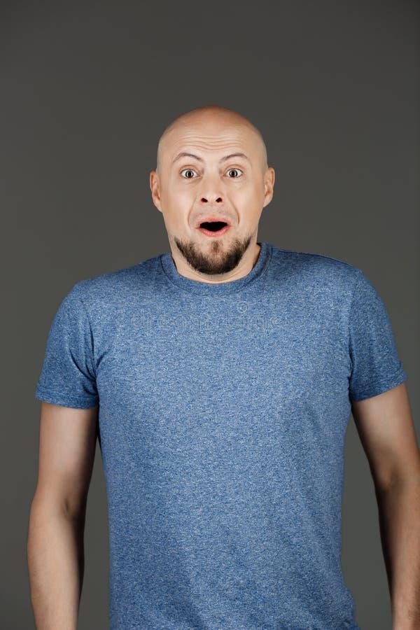 Retrato do homem de meia idade surpreendido considerável na camisa cinzenta sobre o fundo escuro foto de stock