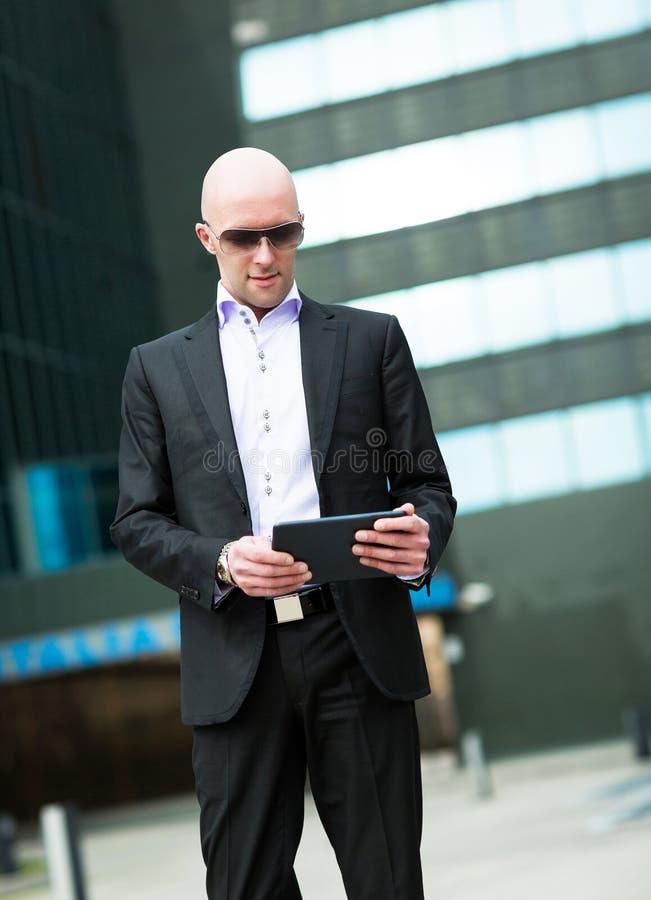 Retrato do homem de negócio de sorriso que usa a tabuleta do computador foto de stock royalty free
