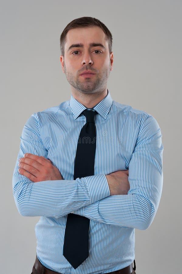 Retrato do homem de negócio na camisa azul com mãos dobradas no cinza fotos de stock royalty free