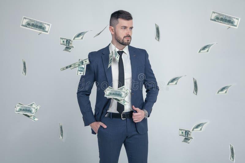 Retrato do homem de negócios à moda com as cédulas de queda do dólar no fundo cinzento vestido em um terno com um penteado à moda imagens de stock