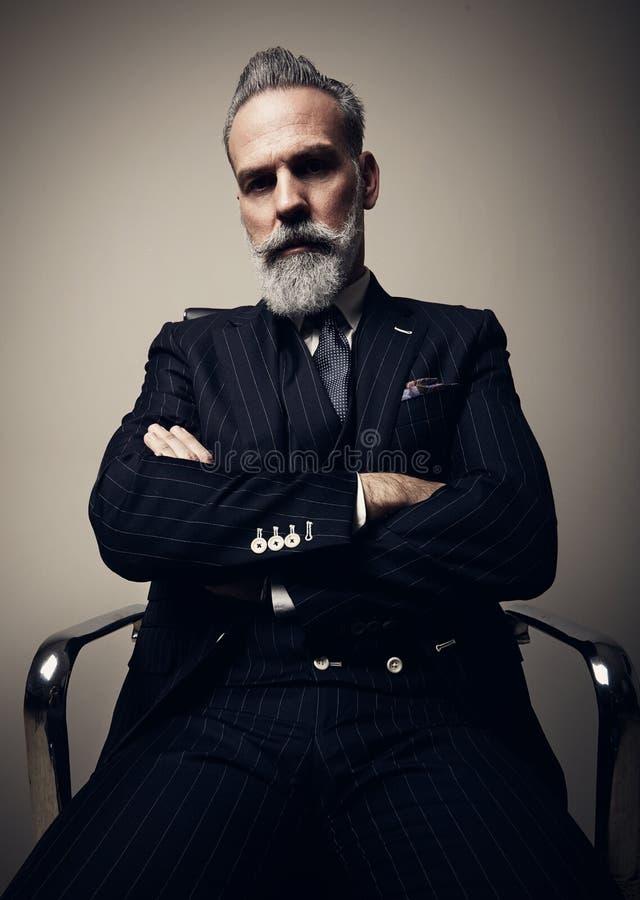 Retrato do homem de negócios adulto sério que veste o terno na moda e que senta-se com os braços cruzados no estúdio na cadeira c imagem de stock royalty free