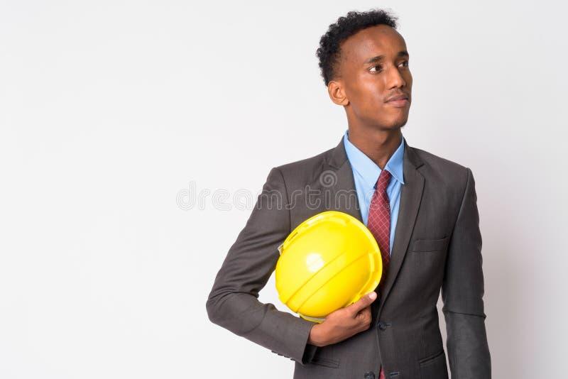 Retrato do homem de negócios africano considerável novo com pensamento do capacete de segurança fotos de stock