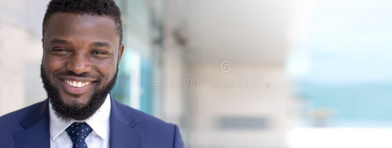 Retrato do homem de negócios africano feliz que olha a câmera fora Espaço longo da cópia imagem de stock