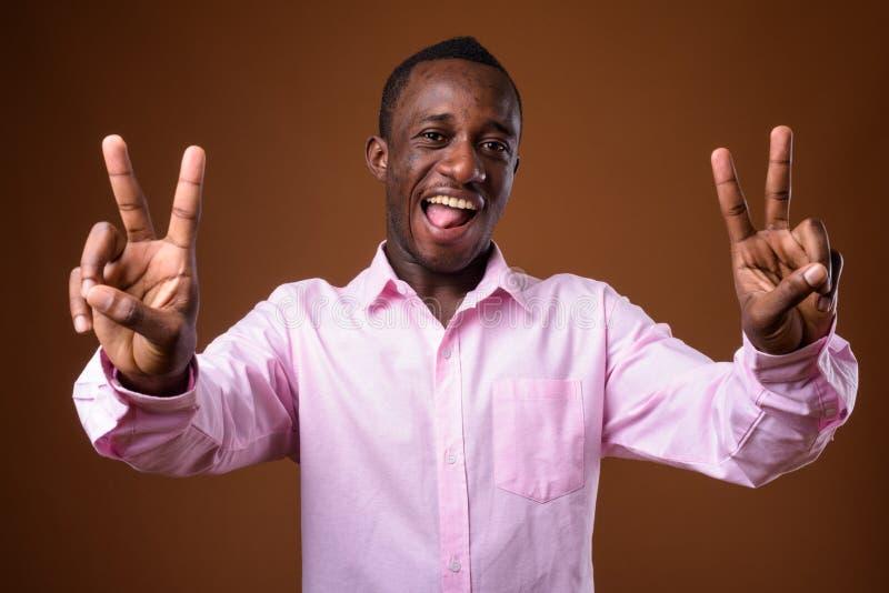 Retrato do homem de negócios africano novo que faz o sinal de paz contra o fundo marrom imagem de stock