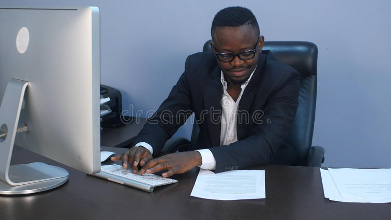 Retrato do homem de negócios afro-americano sério novo que trabalha com portátil e original foto de stock royalty free