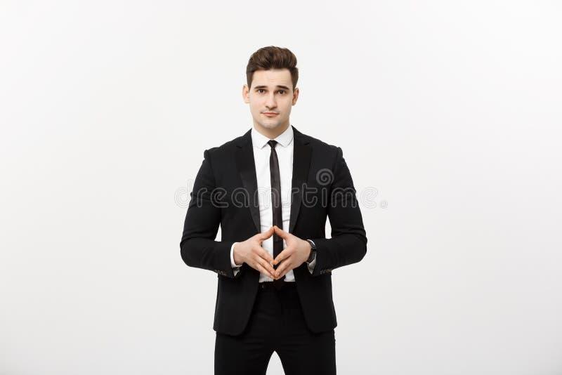 Retrato do homem de negócios alegre, atrativo, considerável que guarda as mãos com a cara segura que olha a câmera que está sobre fotografia de stock