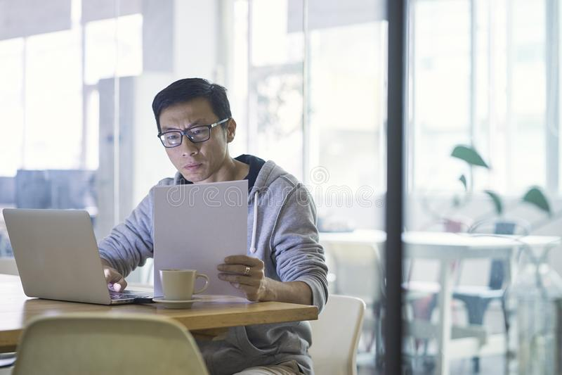 Retrato do homem de negócios asiático que trabalha no portátil no escritório foto de stock