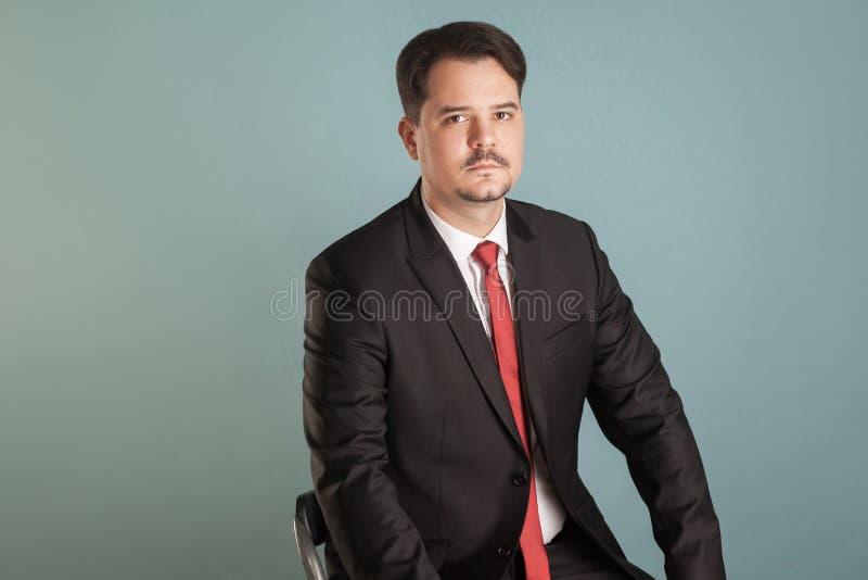 Retrato do homem de negócios de assento do tiro ativo que lookking seriamente foto de stock royalty free