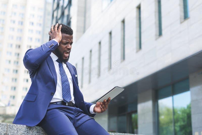 Retrato do homem de negócios chocado que olha a tabuleta ao sentar-se em um ajuste urbano fotos de stock