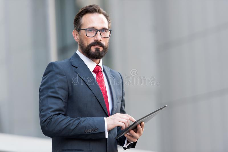 Retrato do homem de negócios com tabuleta à disposição no fundo do prédio de escritórios Homem de negócios que usa a tabuleta ext imagens de stock royalty free