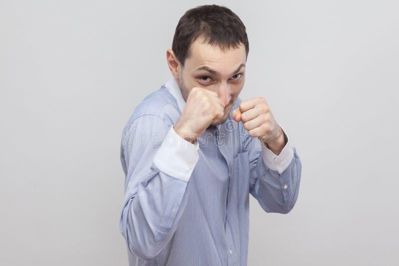 Retrato do homem de negócios considerável irritado da cerda na luz clássica - posição azul da camisa com pose do ataque do encaix foto de stock royalty free