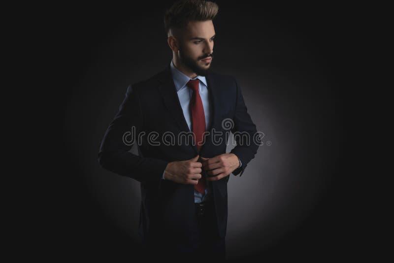 Retrato do homem de negócios curioso no terno da marinha que abotoa o terno imagens de stock royalty free