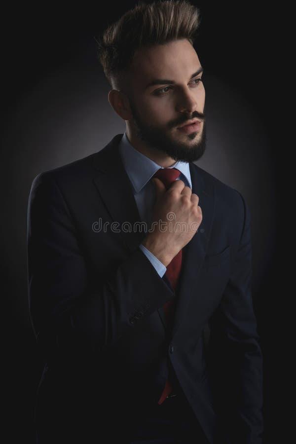 Retrato do homem de negócios curioso que olha laço para tomar partido e fixar fotos de stock