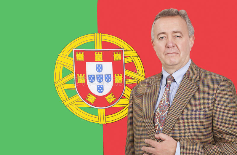 Retrato do homem de negócios de meia idade que está sobre a bandeira portuguesa foto de stock royalty free