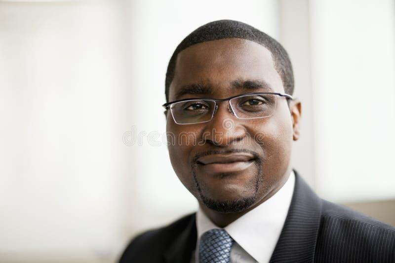 Retrato do homem de negócios de sorriso nos vidros, em principal e em ombros fotos de stock