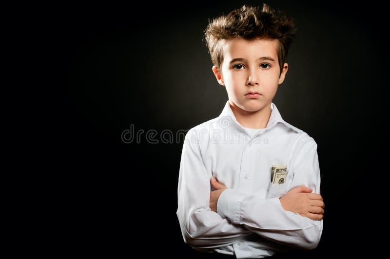 Retrato do homem de negócios do rapaz pequeno na baixa chave com os braços cruzados foto de stock royalty free
