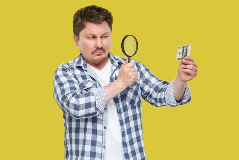 Retrato do homem de negócios envelhecido médio sério do inspetor na camisa quadriculado ocasional que está, guardando e olhando o imagens de stock royalty free