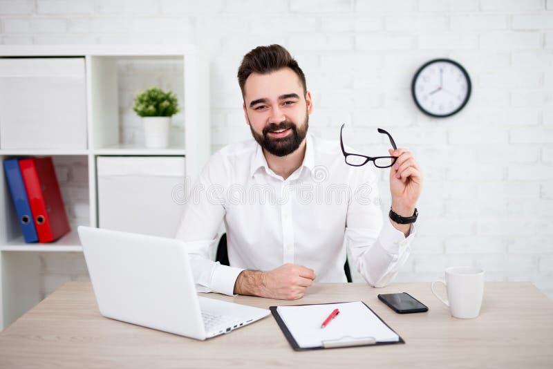 Retrato do homem de negócios farpado alegre que usa o computador no escritório foto de stock royalty free